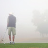 Man golfing in the fog
